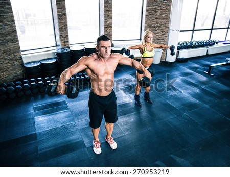 Muscular man and fit woman workout with dumbbells at gym - stock photo