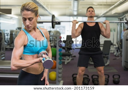 Muscular man and woman lifting weights at the gym