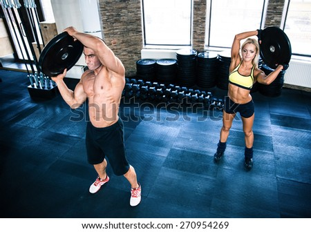 Muscular man and woman workout at crossfit gym - stock photo