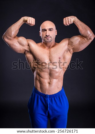 Muscular man bodybuilder is demonstrating his perfect muscular body  muscles and arms. Isolated over dark background.