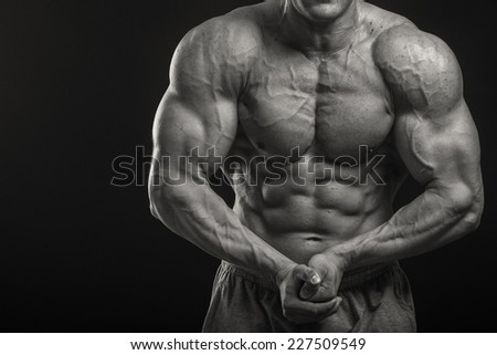 Muscular man bodybuilder. Man posing on a black background, shows his muscles. Bodybuilding, posing, black background, muscles.