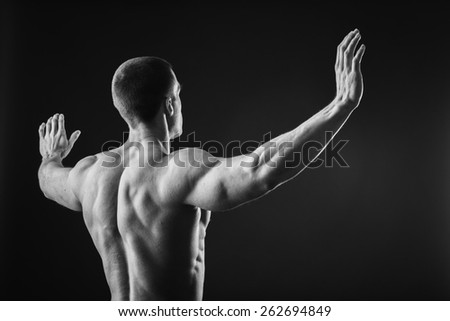 Muscular man bodybuilder. Man posing on a black background, shows his muscles. Bodybuilding, posing, black background, muscles - the concept of bodybuilding. Article about bodybuilding.