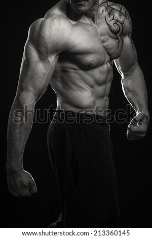 Muscular man bodybuilder with tattoos. Man posing on a black background, shows his muscles. Bodybuilding, posing, black background, muscles - the concept of  - stock photo