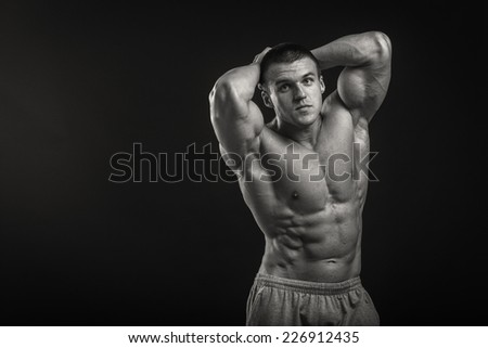 Muscular man bodybuilder with tattoos. Man posing on a black background, shows his muscles. Bodybuilding, posing, black background, muscles. - stock photo