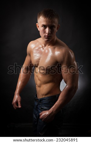 Muscular man covered with water drops on a black background.
