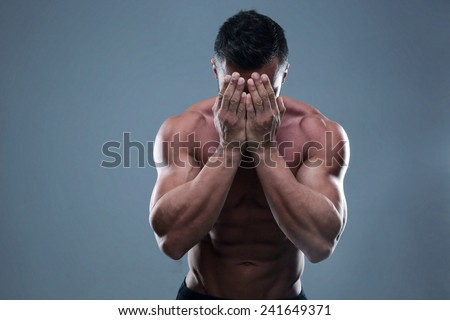 Muscular man covering his face with the hands - stock photo