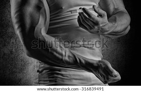 muscular man doing a shot in the biceps, steroids, pharmacology - stock photo