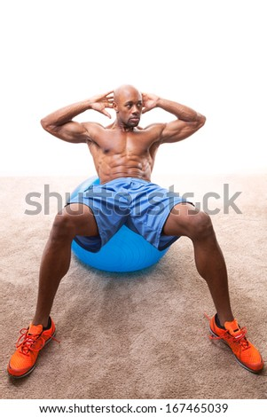 Muscular man doing ab crunches on an exercise ball.   - stock photo
