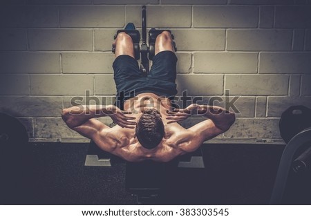 Muscular man doing exercises for abdominal in The Gym's Studio - stock photo