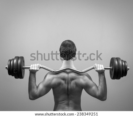 Muscular man doing exercises with barbell. Back view. Black and white. - stock photo