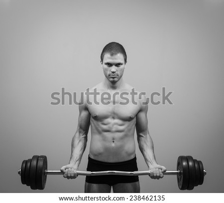 Muscular man doing exercises with barbell. Black and white.