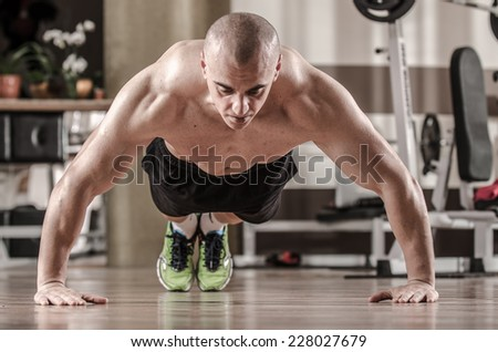 Muscular man doing push ups in a gym  - stock photo