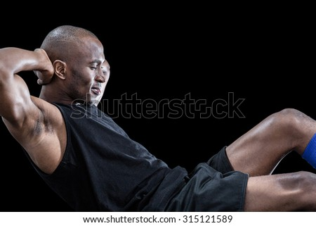 Muscular man doing sit ups with eyes closed against black background - stock photo