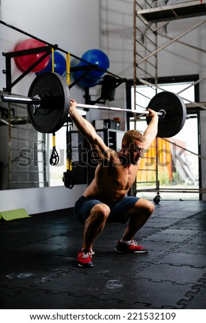 Muscular man doing squats with barbell in a gym - stock photo