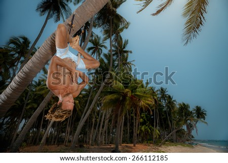Muscular man doing upside down yoga on palm tree - stock photo