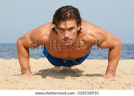 Muscular man during workout on the beach