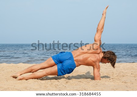 Muscular man during workout on the beach - stock photo