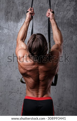 Muscular man during workout with suspension straps
