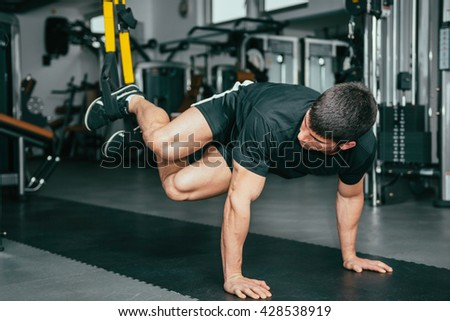 Muscular man exercising in health club. Using TRX bands, doing push-ups and torso rotations with legs suspended. - stock photo