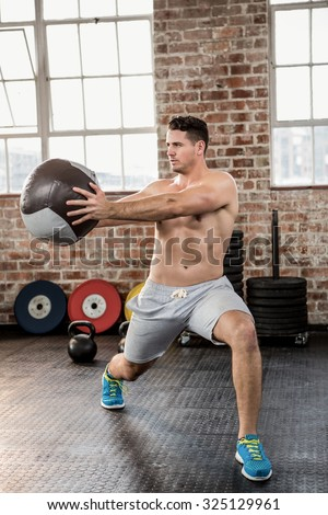 Muscular man exercising with medicine ball at the gym - stock photo