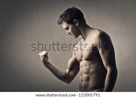 Muscular man flexes his right arm muscle - stock photo