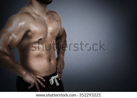 Muscular man flexing for camera against grey