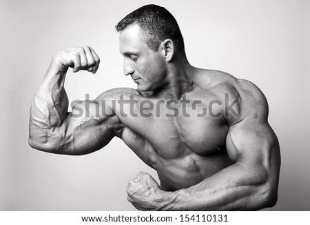 Muscular man flexing his biceps - BW shot - stock photo