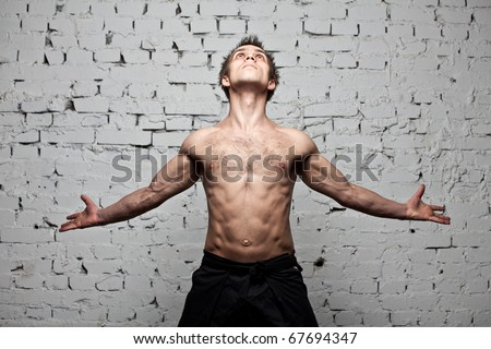 muscular man freedom fly at brick background - stock photo
