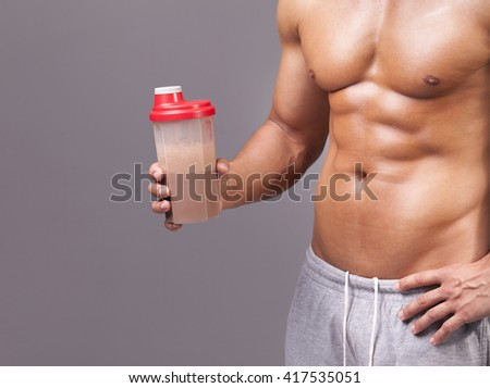 Muscular man holding a shaker with chocolate protein on grey background - stock photo