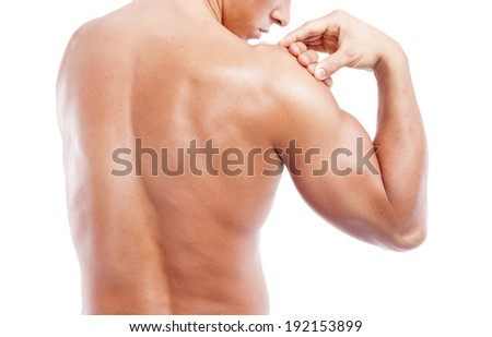 Muscular man holding his shoulder in pain, isolated on white background - stock photo