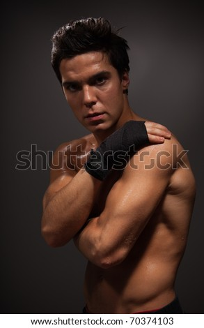 Muscular man holding his shoulder with hands on dark background - stock photo