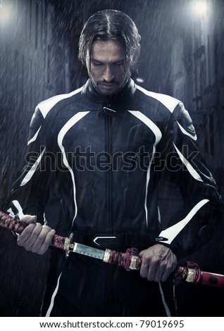 Muscular man holding samurai sword in on a rainy night - stock photo