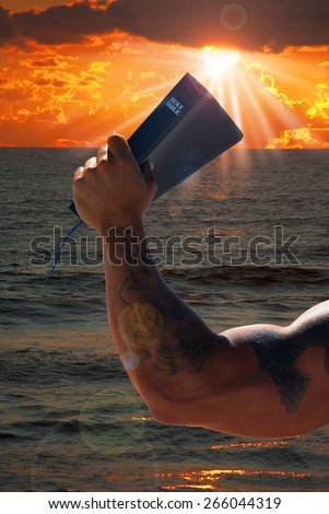 Muscular man holding the Bible high showing strength in faith. - stock photo