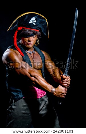 Muscular man in a pirate costume. Aggressive man with a sword on a black background - stock photo