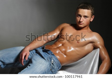 muscular man in blue jeans and an athletic, brilliant torso - stock photo