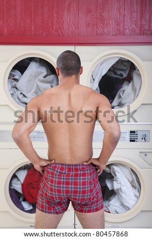 Muscular man in boxer shorts waits in front of washing machines - stock photo