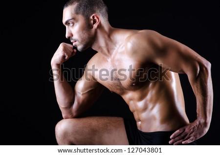 Muscular man in dark studio - stock photo