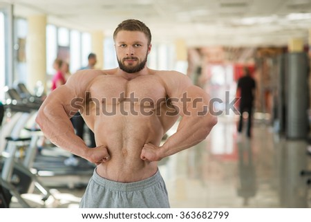 Muscular man in gym. Strong muscular man looking straight at the camera. Bodybuilder showing his huge muscles. - stock photo