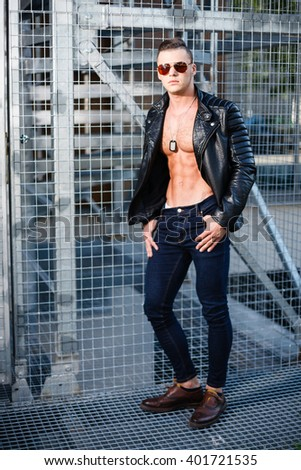 Muscular man in leather jacket and sunglasses. Industrial portrait. - stock photo