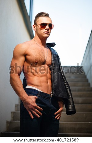 Muscular man in leather jacket and sunglasses on stairs. - stock photo