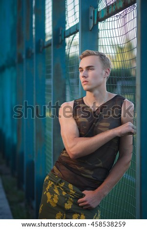 Muscular man in military pants outdoor fashion shoot - stock photo