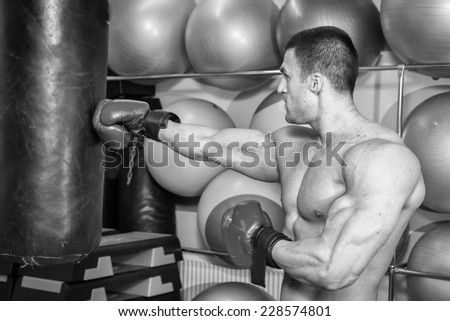 Muscular man in the gym. The man in boxing gloves, hit a punching bag, exercise. Boxing, workout, muscle, strength, power - the concept of strength training and boxing - stock photo