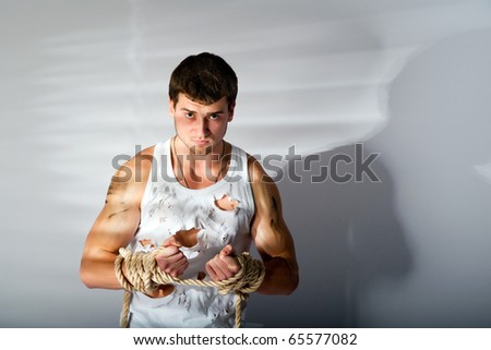 muscular  man in torn white top and jeans - stock photo