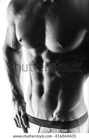 Muscular man in underpants on white isolated background. Close up of a handsome man's torso. Closeup sport body only. Strong muscular athlete male bodybuilder. Force, power. Monochrome. - stock photo