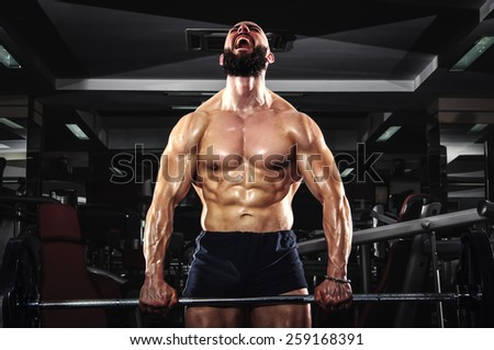 Muscular Man Lifting Some Heavy Barbells - stock photo