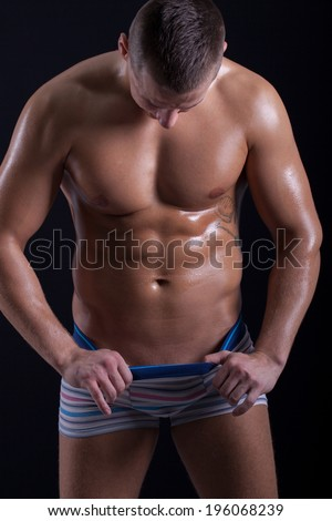 muscular  man looking down in his pants  - stock photo
