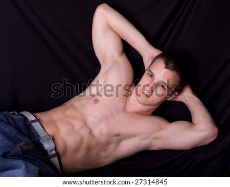 muscular man lying on bed - stock photo