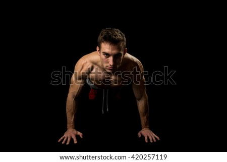 Muscular man making pushups in studio, isolated on black background