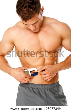 Muscular man measures level of fat on his body on white background - stock photo