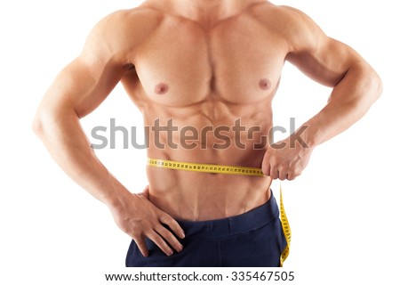 Muscular man measuring his waistline